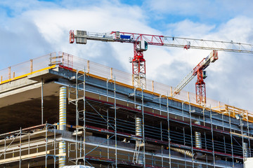 Construction site with crane and building against blue sky