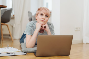 Thoughtful woman working with laptop on floor