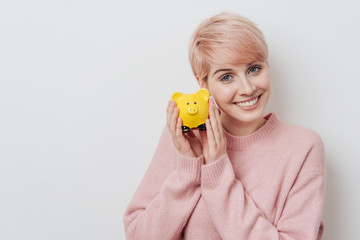 Successful young woman holding a piggy bank