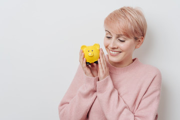 Young woman holding a bright yellow piggy bank