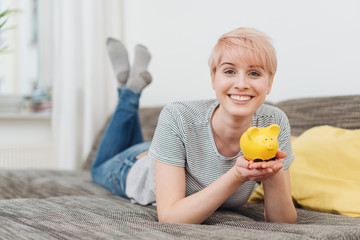 Cute vivacious young woman holding a piggy bank