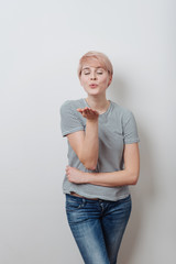 Romantic attractive young woman blowing a kiss