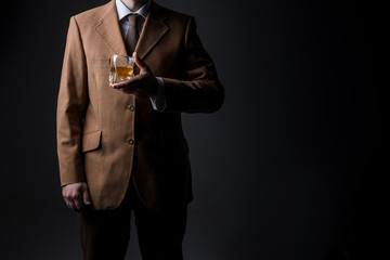 Man in suit with whiskey glass on dark background. No face