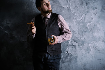 Man in vest standing, leaning against the wall, holding a glass of whiskey (highball)