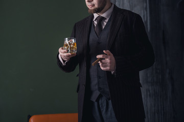 Man in expensive suit is holding whiskey glass in luxury interior. No face