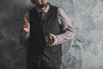 Man in vest standing, leaning against the wall, holding a glass of whiskey. No face