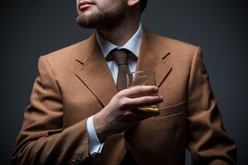 Handsome bearded businessman is drinking expensive whisky closeup. No face