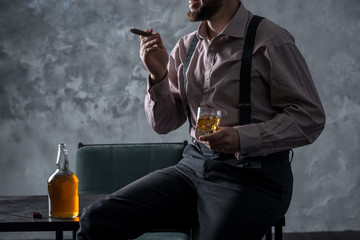 Stylish bearded man sits on the table and drinking whiskey, smoking cigar
