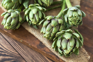Artichoke bouquets on sackcloth on wooden background