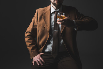 Man in expensive suit is drinking whisky. No face