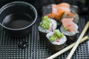 Fresh and delicious maki and nigiri sushi rolls with tiger shrimps, salmon, philadelphia cheese and wasabi served with soy sauce and ginger slices on black take away plate. Japanese food in restaurant