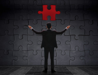 Problem in Work Concept. Businessman Standing in front of blank Jigsaw Puzzle Wall to Finding a Lost Piece. Teamwork or Human Resource
