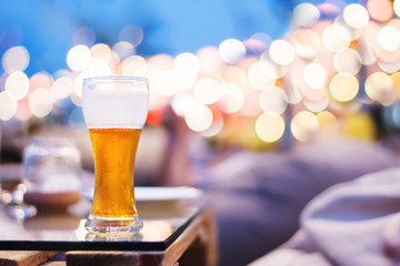 Drinking Alcohol  in Summer Night Party or Event Concept. Glass of Beer on Table. Blurred Light Bokeh as background