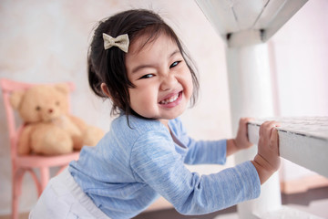 Lovely Kids Portrait, a Happy 2 Years Old Child Smiling and looking at camera. Playful Little Girl Playing Hide and Seek Game