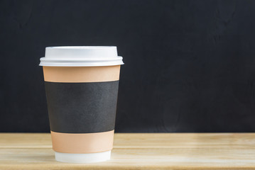 coffee to go. One paper coffee cups on wooden background.