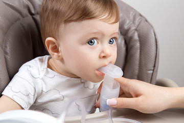 Mother using nebulizer for cute little baby boy sitting on the high chair. Health care concept.