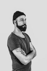 Portrait eines Mannes mit Bart , Mütze auf dem Kopf und Tattoos auf dem Arm in Schwarz/weiß