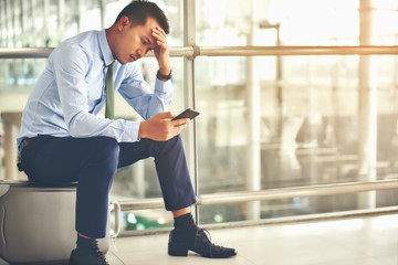 An Asian businessman is sitting on his luggage. He was stressed and looked at his smartphone at the airport.
