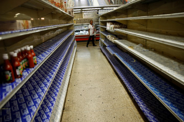 A woman looks at the almost empty shelves while she looks for groceries and goods in a supermarket in Caracas