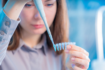Young woman cutting of sample from pcr microtube rack