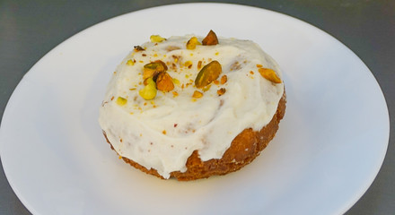 A Pistachio Covered Cream Cheese Iced Cake Doughnut on a white plate