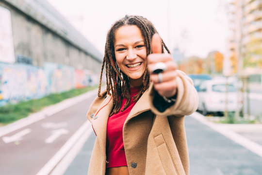 young woman outdoors posing thumbs up