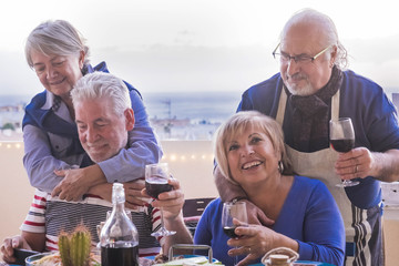 group of senior friends eat together outdoor