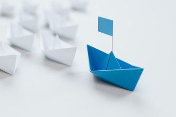 Leadership concept with red paper ship leading among white on white background.3d rendering.