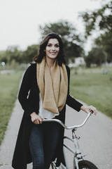 Portrait of smiling woman with bicycle at park
