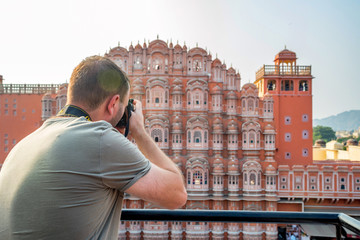 Male traveler takes picture of Hawa Mahal in India