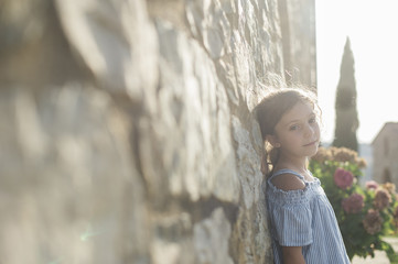 Portrait of girl leaning on wall in city