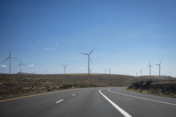Empty road and windmills against blue sky during sunny day