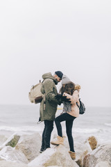 Side view of couple with backpacks standing on rocks at beach by sea against clear sky