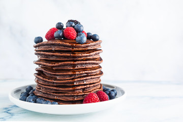 chocolate pancake breakfast for pancake day with fresh berries and sauce.