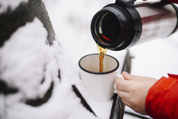 Cropped hands of woman pouring black coffee from insulated drink container into mug on snow