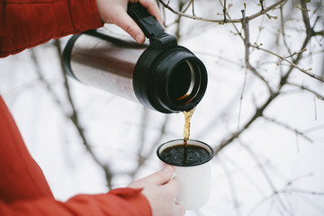 Close-up of woman pouring black coffee from insulated drink container into mug during winter