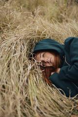 High angle thoughtful of teenage girl lying on grassy field