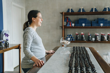 Smiling pregnant woman standing near table in shop