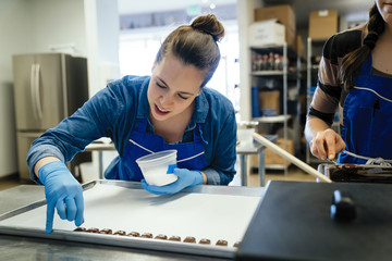 Midsection of female chef standing by coworker garnishing chocolate pieces in tray at factory