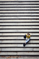 High angle view of woman with phone sitting on steps at park