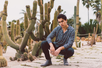 Young man sitting at cactus