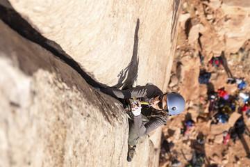 High angle view of female rock climber climbing rock