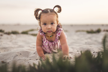 Portrait of cute baby girl crawling on sand at beach