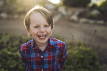 Portrait of cheerful boy standing at park