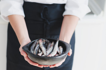 Little fishes in ceramic bowl over chef's hands.