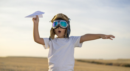 Little boy wearing helmet and dreams of becoming an aviator while playing a paper plane at sunset Wall mural