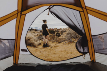 Side view of woman looking away while standing on field seen through tent