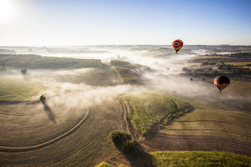 Aerial view of hot air balloons flying over landscape against sky during sunny day