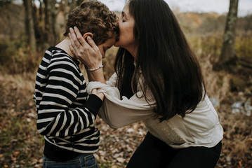 Side view of mother kissing on son's head at park