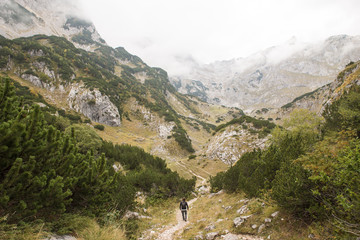 Rear view of man walking on trail amidst mountains against sky at Durmitor National Park
